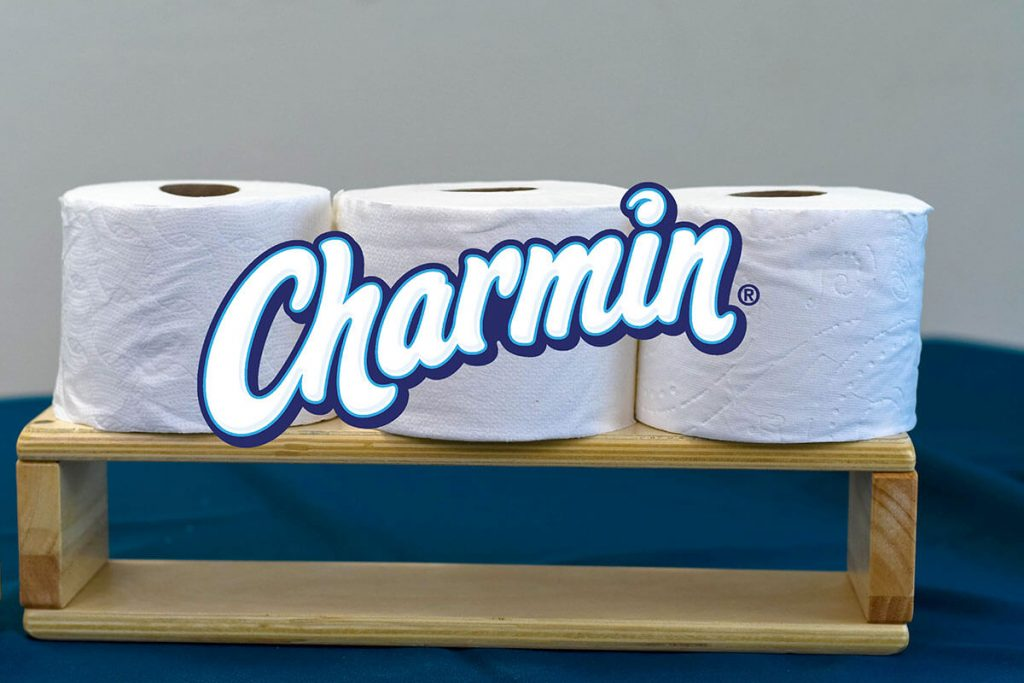 Charmin toilet paper rolls on log.