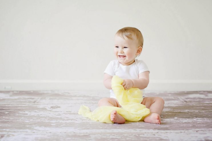 Baby smiling and sitting down.